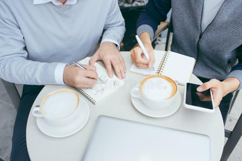 Zwei junge Gesch?ftsm?nner plaudern in einer Kaffeestube - Bild stockbilder