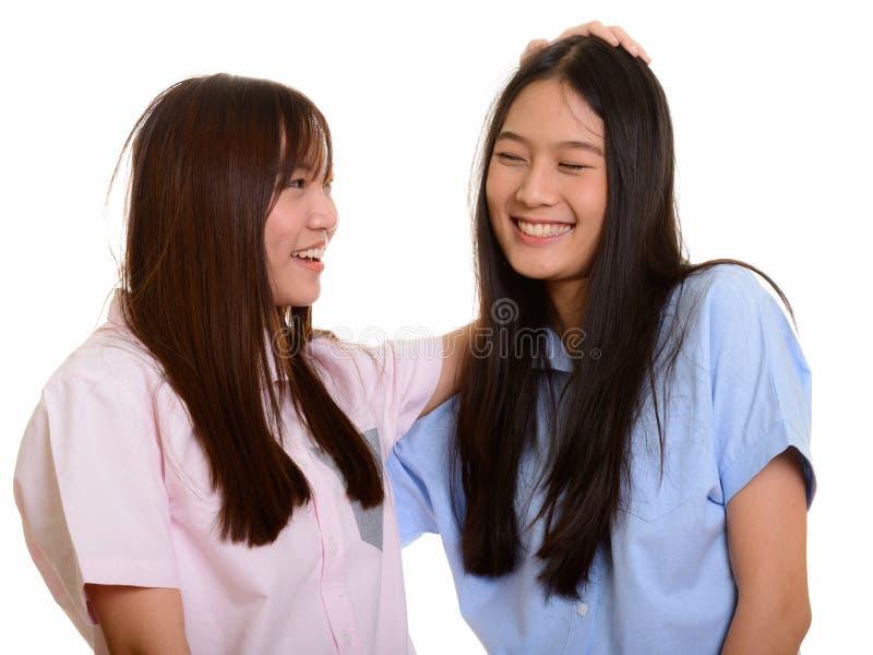 Zwei junge glückliche asiatische Jugendlichen, die ihr frie lächeln und tappen lizenzfreies stockfoto