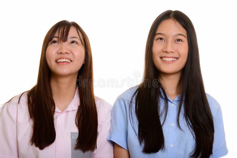 Zwei junge glückliche asiatische lächelnde und denkende Jugendlichen lizenzfreies stockbild