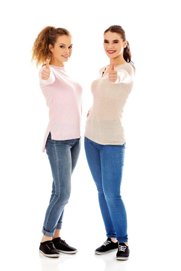 Zwei junge glückliche Frauen, die sich Daumen zeigen lizenzfreie stockfotos