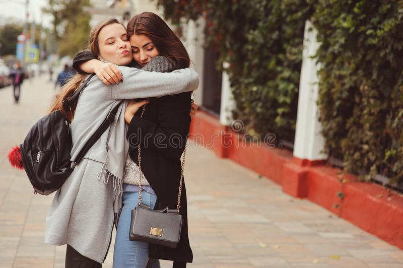 Zwei junge glückliche Freundinnen, die auf Stadtstraßen in den zufälligen Modeausstattungen gehen stockbilder