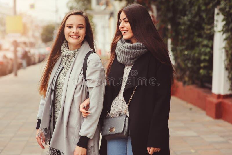 Zwei junge glückliche Freundinnen, die auf Stadtstraßen in den zufälligen Modeausstattungen gehen stockfotografie