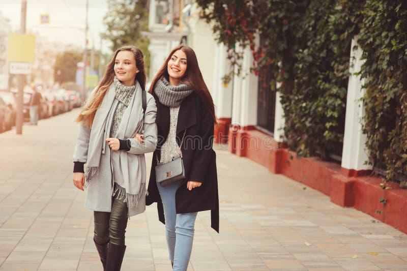 Zwei junge glückliche Freundinnen, die auf Stadtstraßen in den zufälligen Modeausstattungen gehen lizenzfreie stockbilder