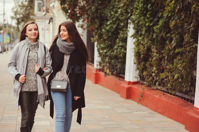 Zwei junge glückliche Freundinnen, die auf Stadtstraßen in den zufälligen Modeausstattungen gehen stockfoto