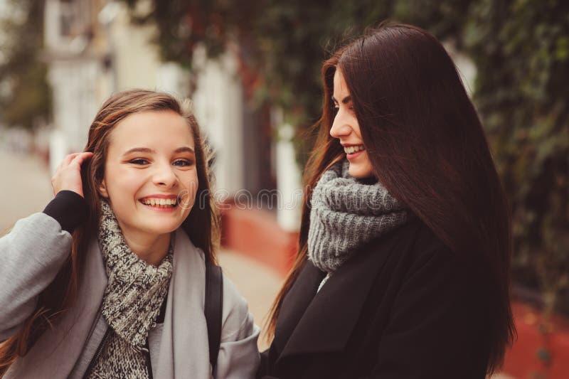 Zwei junge glückliche Freundinnen, die auf Stadtstraßen in den zufälligen Modeausstattungen gehen stockfotos