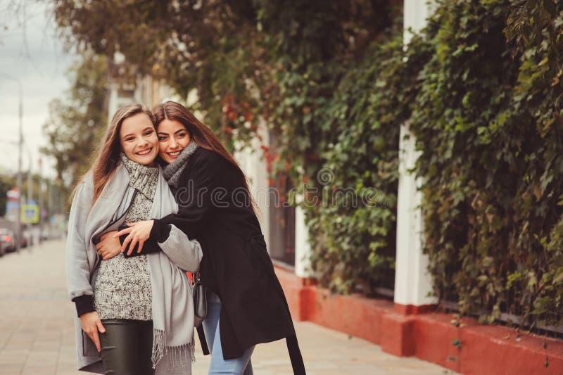Zwei junge glückliche Freundinnen, die auf Stadtstraßen in den zufälligen Modeausstattungen gehen lizenzfreies stockbild