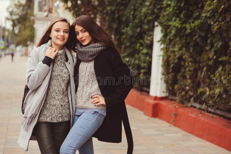 Zwei junge glückliche Freundinnen, die auf Stadtstraßen in den zufälligen Modeausstattungen gehen lizenzfreie stockfotografie