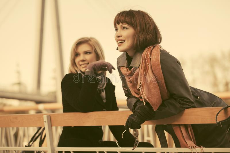 Zwei junge glückliche Modefrauen auf der Bank in der Stadtstraße stockfotos
