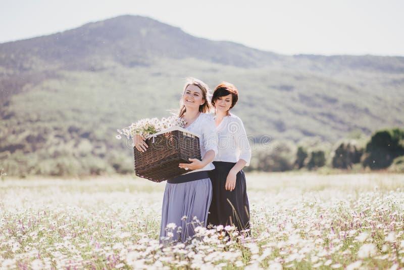 Zwei junge hübsche Frauen, die auf einem Kamillengebiet aufwerfen lizenzfreie stockfotos