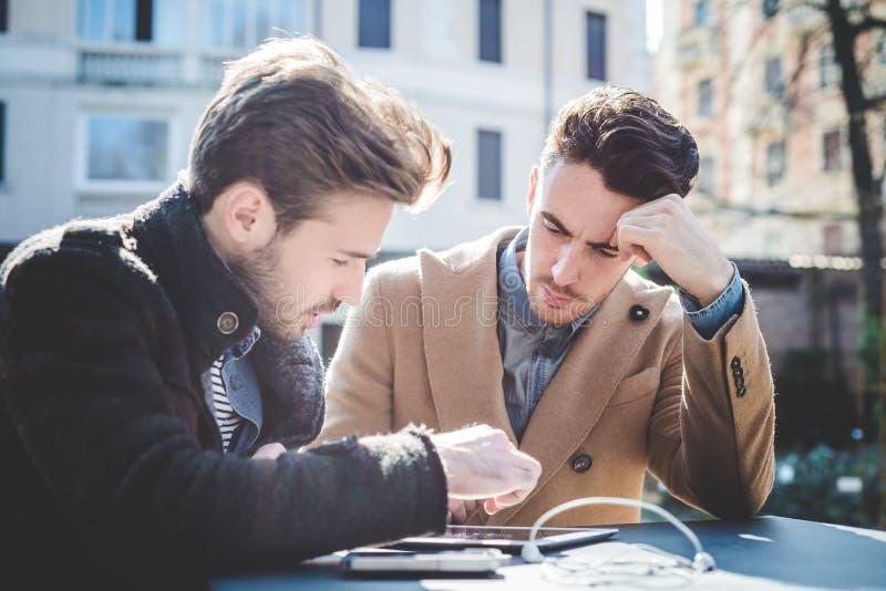 Zwei junge hübsche Geschäftsmänner unter Verwendung der Tablette lizenzfreie stockbilder