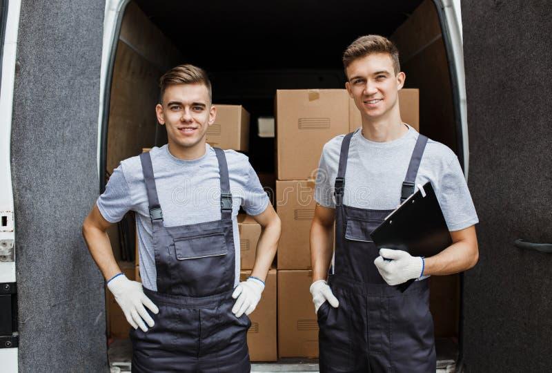 Zwei junge hübsche lächelnde Arbeitskräfte, die Uniformen tragen, stehen vor dem Packwagen voll von Kästen Hausbewegung, Urheber lizenzfreie stockfotografie