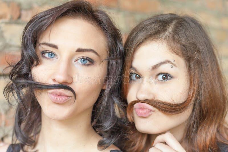 Zwei junge hübsche Mädchen, die Schnurrbart von ihrem Haar herstellen stockbild