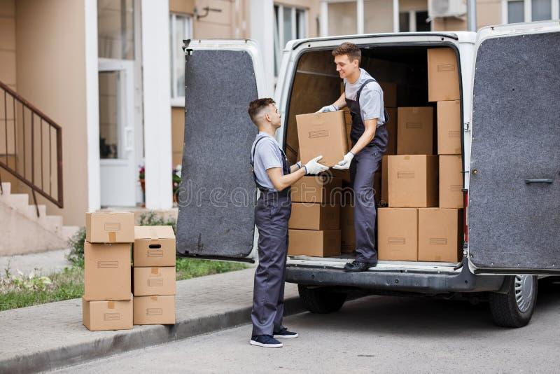 Zwei junge hübsche Urheber, die Uniformen tragen, entladen den Packwagen voll von Kästen Hausbewegung, Urheberservice stockbild