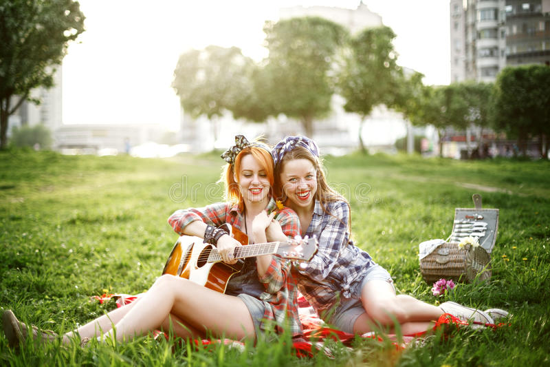 Zwei junge Hippie-Mädchen, die Spaß auf dem Picknick haben lizenzfreies stockfoto