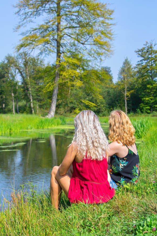 Zwei junge kaukasische Frauen sitzen zusammen am Ufer lizenzfreie stockbilder