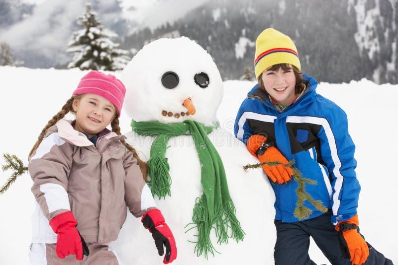 Zwei junge Kinder, die Schneemann am Ski-Feiertag aufbauen stockfotos