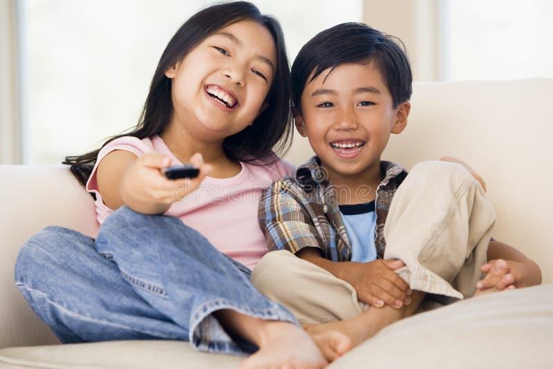 Zwei junge Kinder im Raum mit Fernsteuerungs stockfotografie