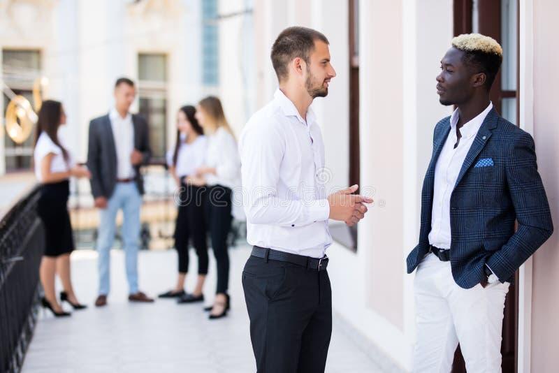 Zwei junge Kollegen, die in der Front ihr Geschäftsteam besprechend schauen lizenzfreies stockbild