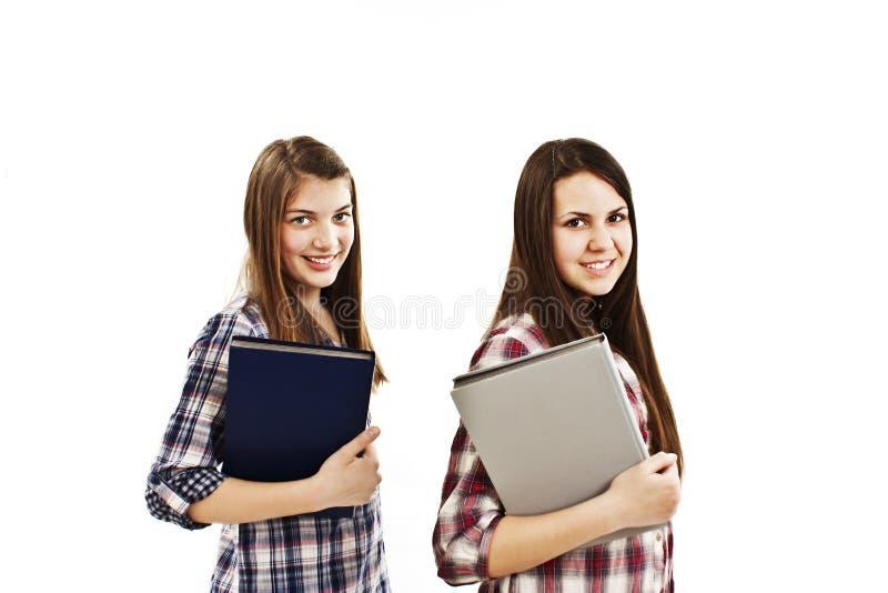 Zwei junge Kursteilnehmer, die ein Buch und ein Lächeln anhalten lizenzfreie stockfotos