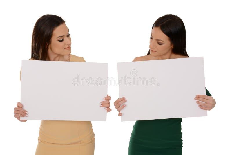 Zwei junge lächelnde Frauen, die zwei Blätter Papier leeres Papier, schauend unten auf Papieren halten lizenzfreies stockbild