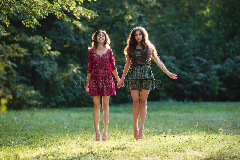Zwei junge lächelnde Frauen schweben frei stockfotografie