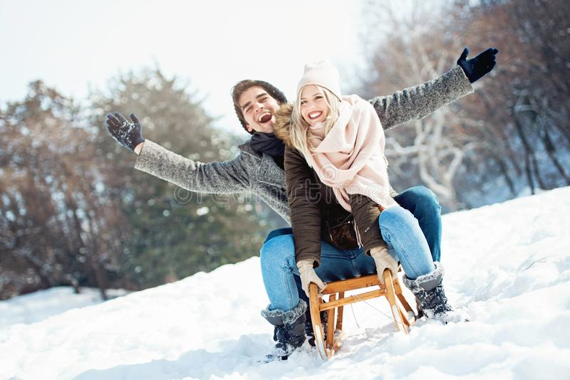 Zwei junge Leute, die auf einen Schlitten schieben stockbilder