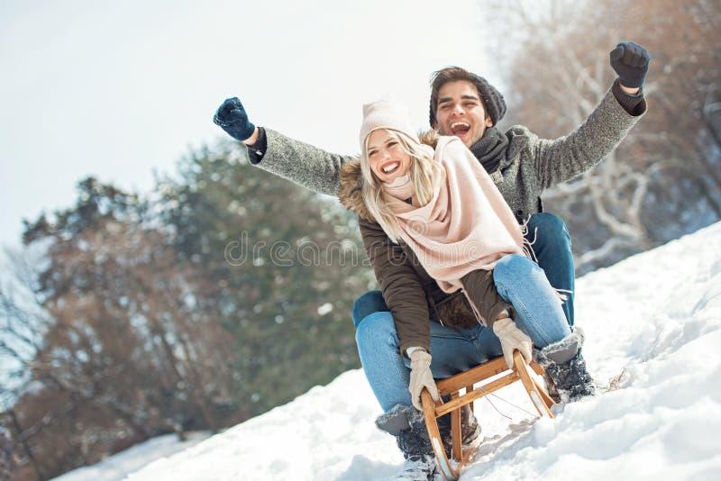 Zwei junge Leute, die auf einen Schlitten schieben stockfotografie