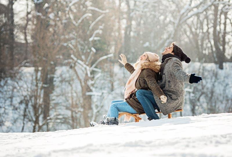 Zwei junge Leute, die auf einen Schlitten schieben lizenzfreies stockfoto