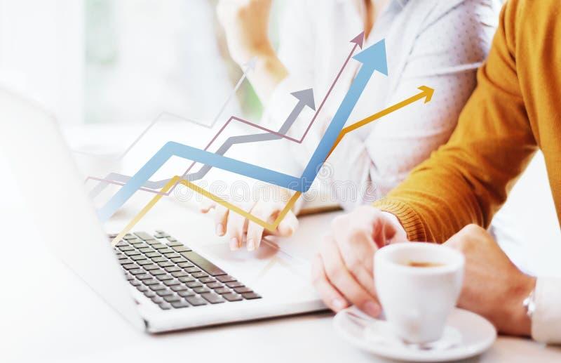 Zwei junge Leute, die einen Laptop mit der Grafik zeigt Wachstum verwenden lizenzfreie stockfotografie