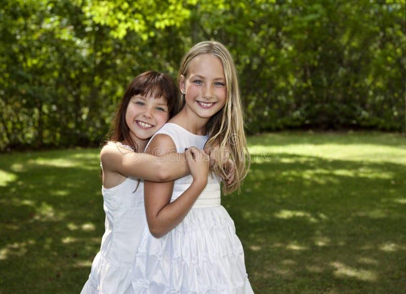 Zwei junge Mädchen in den weißen Kleidern stockfotografie