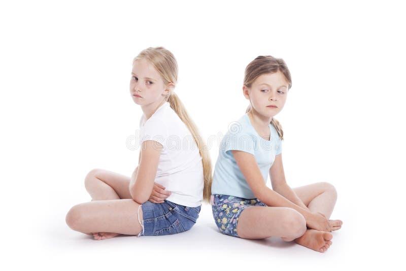 Zwei junge Mädchen, die einen Widerspruch haben stockfotografie