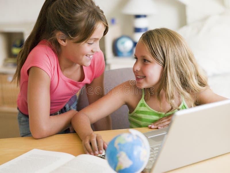 Zwei junge Mädchen, die Heimarbeit auf einem Laptop tun lizenzfreie stockfotos