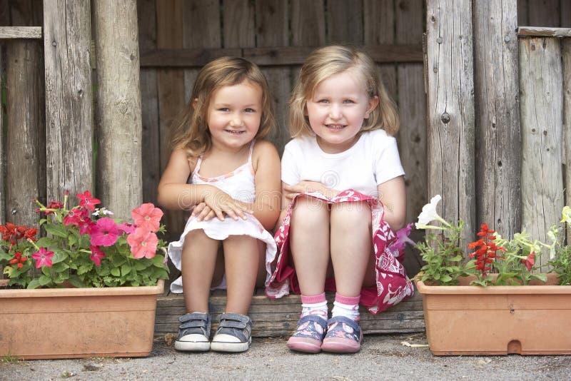 Zwei junge Mädchen, die im hölzernen Haus spielen lizenzfreie stockfotos