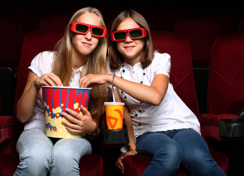 Zwei junge Mädchen, die im Kino überwachen lizenzfreies stockfoto