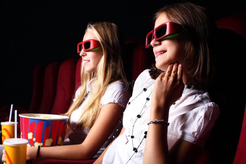 Zwei junge Mädchen, die im Kino überwachen lizenzfreie stockfotos