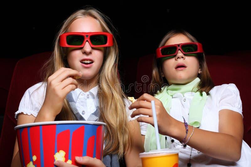 Zwei junge Mädchen, die im Kino überwachen lizenzfreie stockfotografie