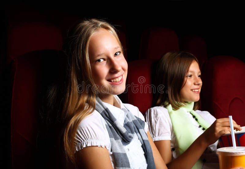 Zwei junge Mädchen, die im Kino überwachen stockfoto