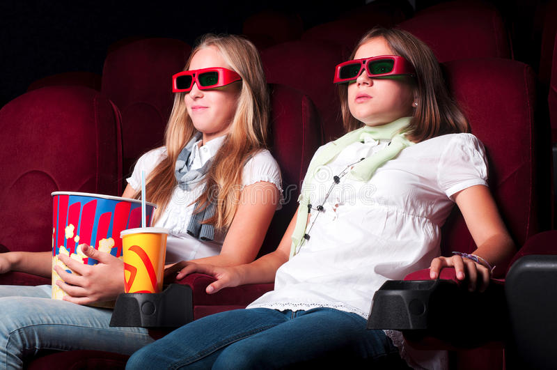 Zwei junge Mädchen, die im Kino überwachen lizenzfreie stockbilder