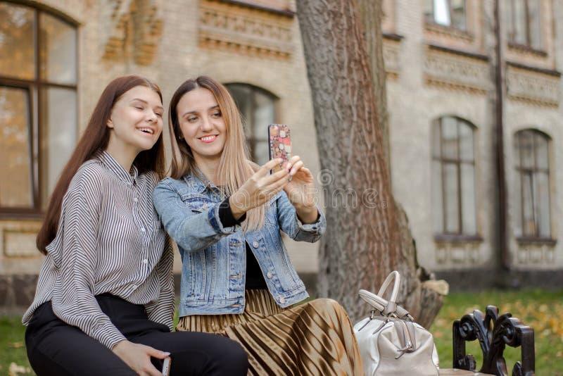 Zwei junge Mädchen, die selfie am Telefon beim Sitzen auf einer Bank im Herbstpark nahe der Universität nehmen stockbilder