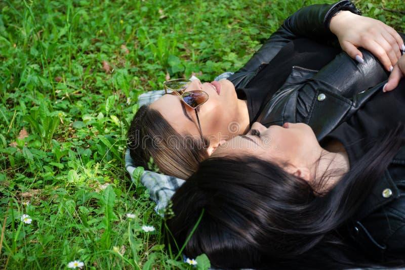 Zwei junge Mädchen, die sich auf der Decke hinlegen und in einer grünen Wiese an einem Frühlingstag in der Natur sprechen stockfotografie