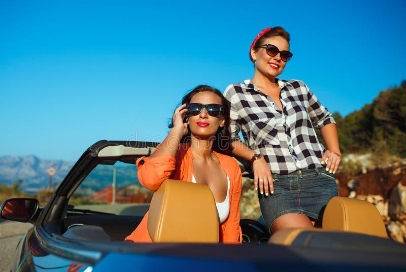 Zwei junge Mädchen, die Spaß im Cabriolet draußen haben lizenzfreie stockbilder