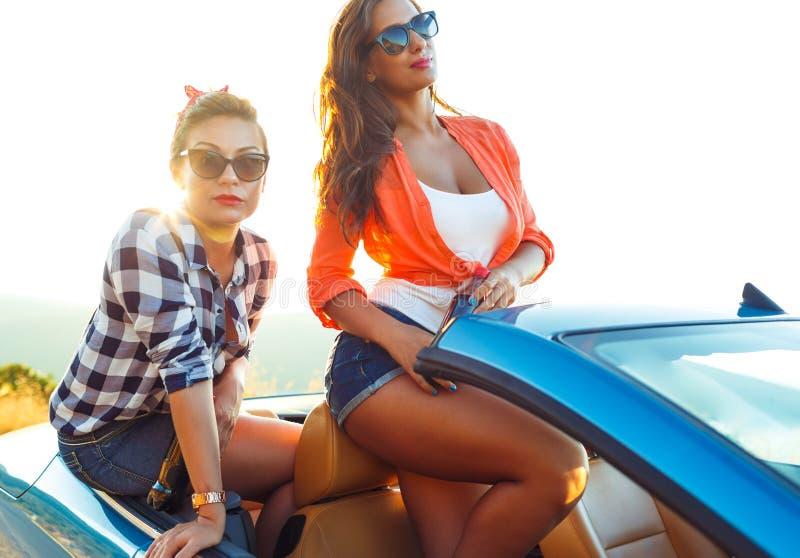 Zwei junge Mädchen, die Spaß im Cabriolet draußen haben stockfoto