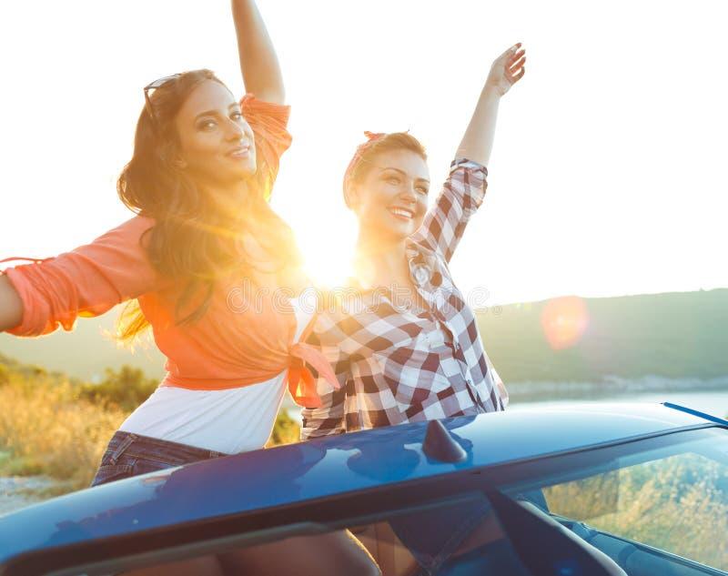 Zwei junge Mädchen, die Spaß im Cabriolet draußen haben lizenzfreies stockbild