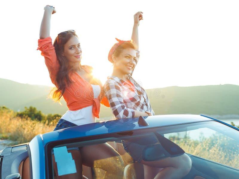 Zwei junge Mädchen, die Spaß im Cabriolet draußen haben stockbilder