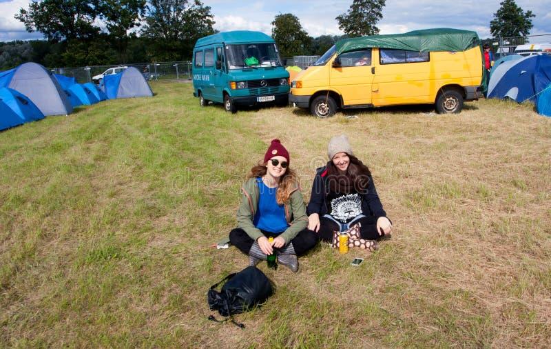 Zwei junge Mädchen haben Rest auf dem Musikfestival stockfotos