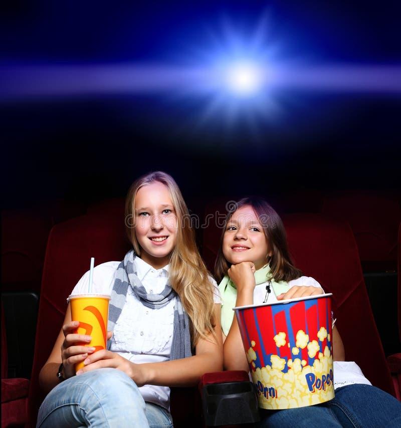 Zwei junge Mädchen im Kino lizenzfreie stockbilder
