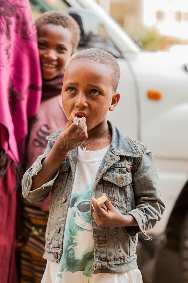 Zwei junge Mädchen mit ihrer Mutter, die einen Snack auf einem ruhigen St. genießt stockfoto