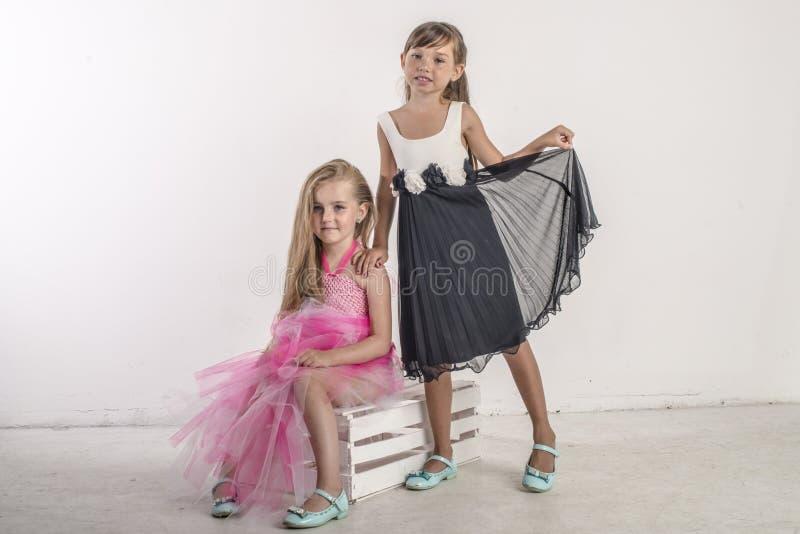 Zwei junge Mädchen sitzen im festlichen Gesang ihrer Schwester stockfotografie