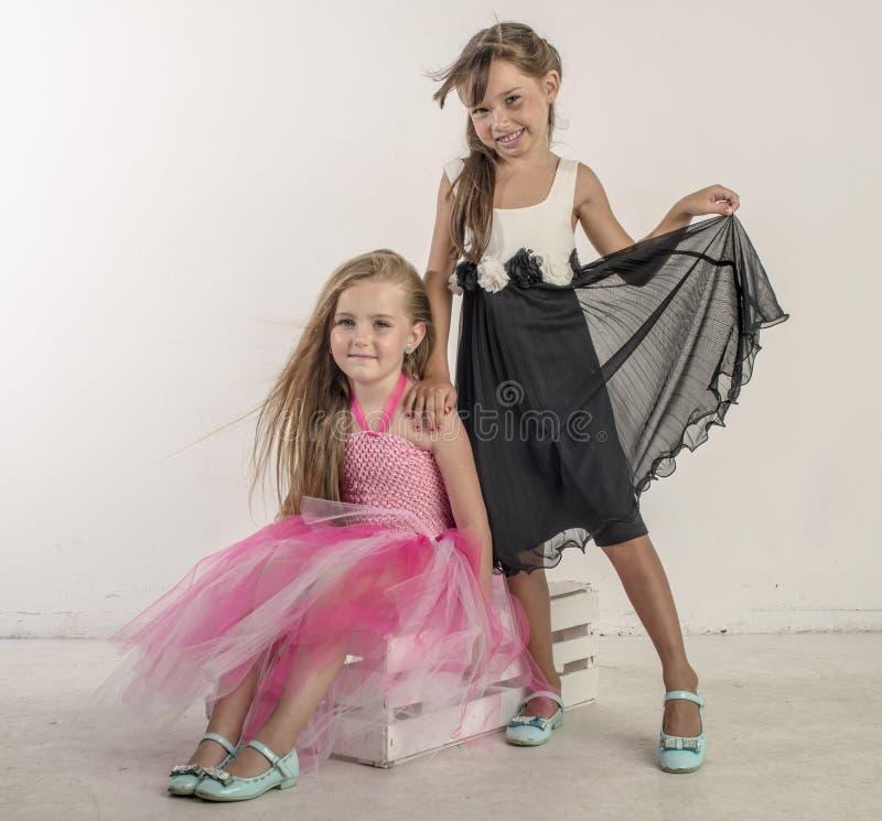 Zwei junge Mädchen sitzen im festlichen Gesang ihrer Schwester lizenzfreies stockfoto