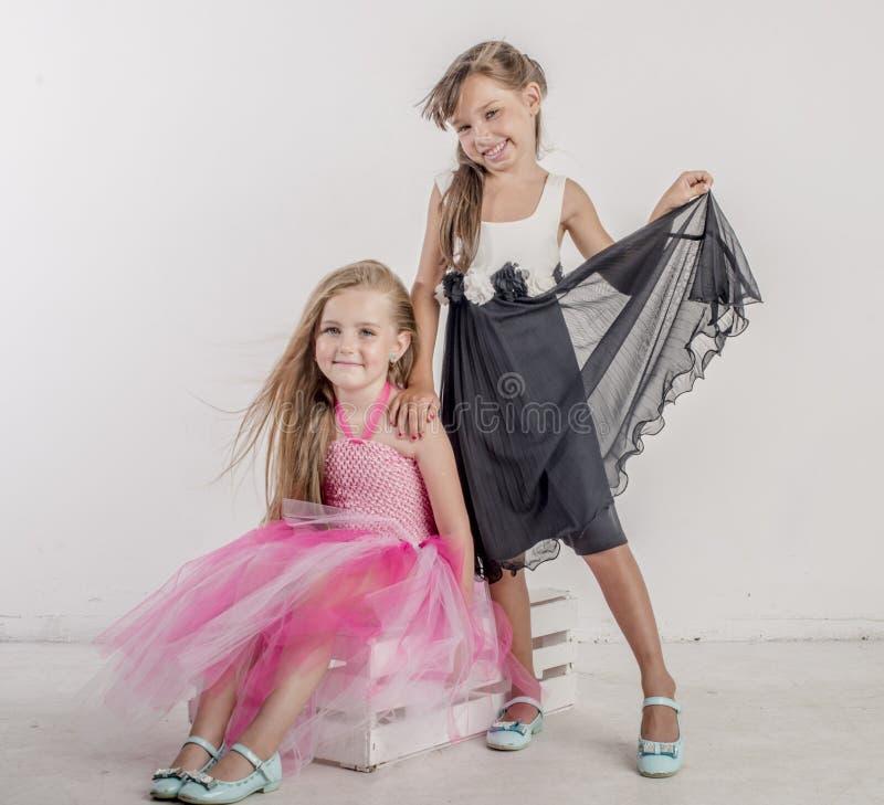 Zwei junge Mädchen sitzen im festlichen Gesang ihrer Schwester lizenzfreie stockfotos